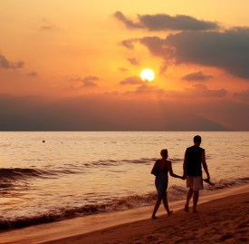 Couple walking along beach at sunset